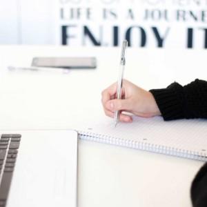 Laptop och person som antecknar på block med en penna